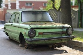 severely damaged old green car