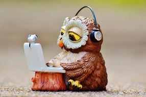 A figure in the shape of an owl that works with a laptop in headphones
