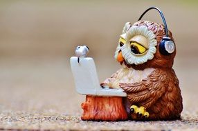 toy owl with headphones and laptop