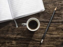 cup of coffee mug pen notebook