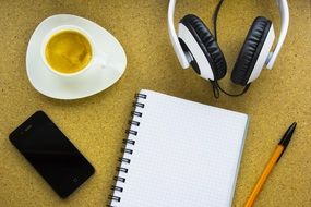 an iphone, headphones, a cup of coffe and a notebook lying on a table