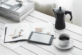On the table lie a tablet, coffee, coffee maker and magazines
