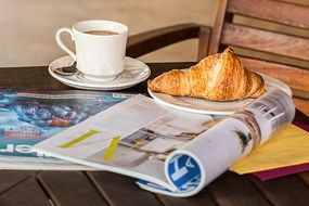 coffee break with croissant and magazine
