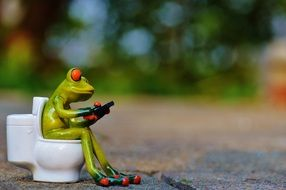frog with mobile phone in the toilet