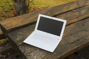white laptop on a wooden table in nature
