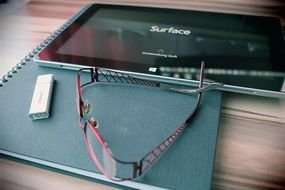 reading glasses, usb stick and tablet