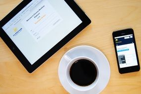 top view of a cup of coffee on the office desk on the background of the smartphone and tablet