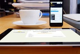 side view of a cup of coffee on the office desk on the background of the iphone and tablet