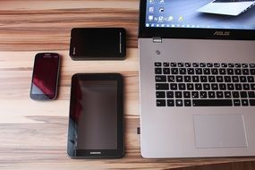 Laptop, smartphone, mobile phones on a wooden table