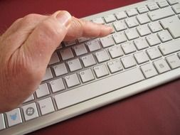 Man is typing on the white keyboard