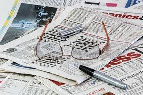 Glasses and a pen lie on the newspapers