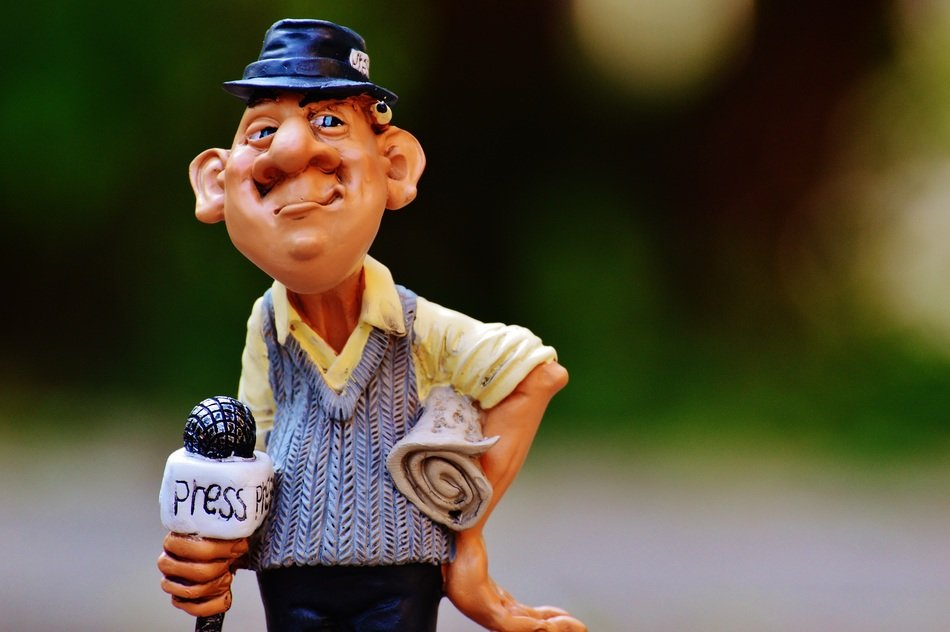 statue of small journalist holding a microphone