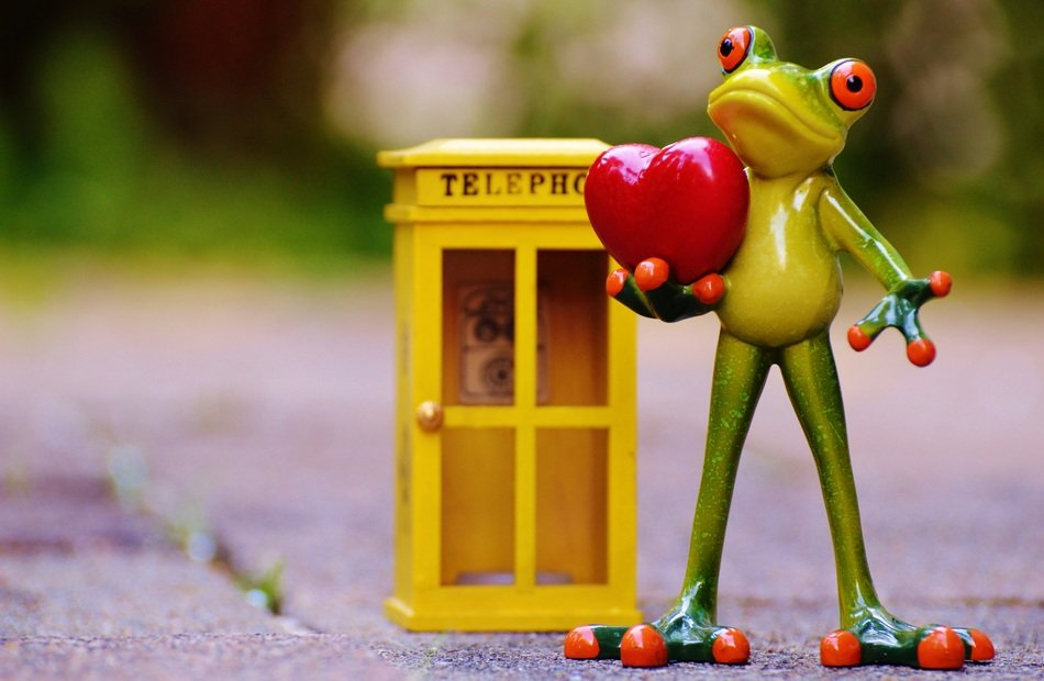 small statue of a green frog holding a heart and standing next to a telephone booth