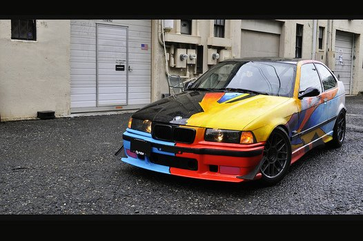 multi-colored BMW stands on the road