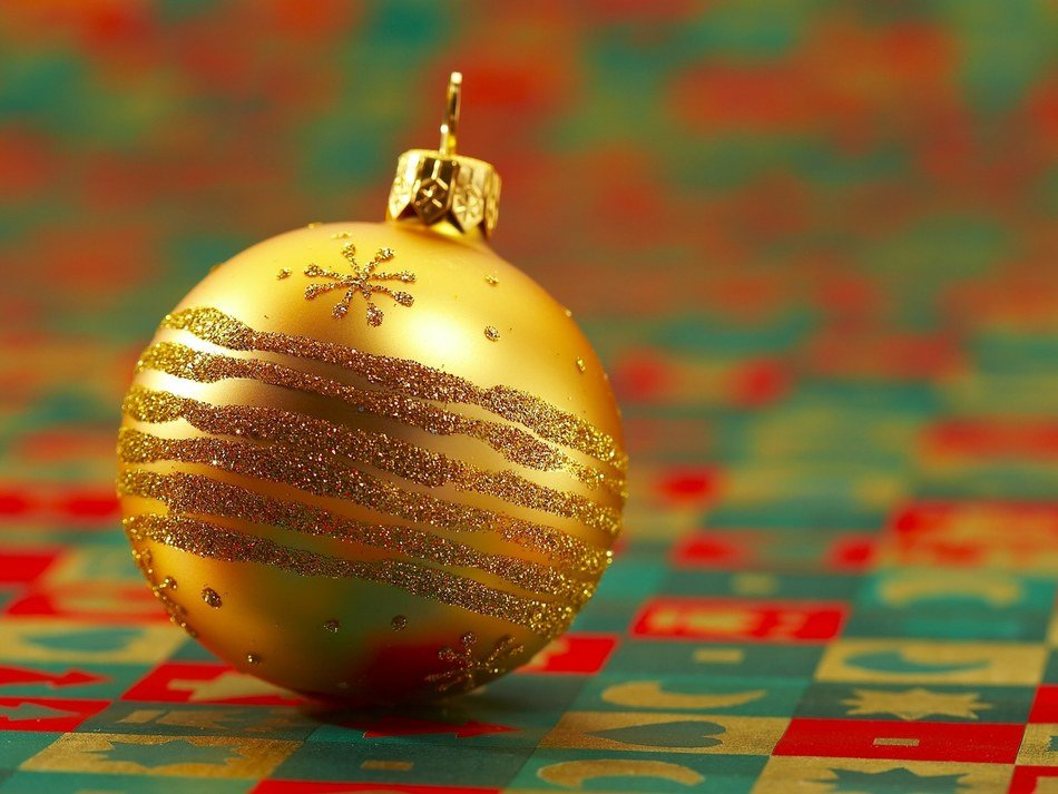 macro view of golden christmas ball on a multi-colored tablecloth