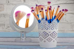 makeup brushes in a white decorative glass on the table