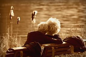 monochrome photo of an elderly couple on a bench by the lake