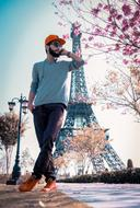 photo of a fashionable young man against the backdrop of the Eiffel Tower