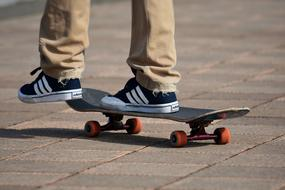 feet of a teenager in adidas sneakers on a skateboard