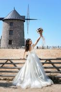 Bride with bouquet at wooden fence in countryside