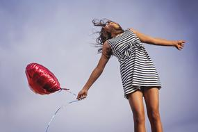 girl in a striped dress with a balloon