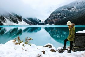 Woman on the beautiful snowy landscape with the lake