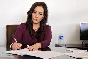 business lady signs a document