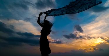 silhouette of a girl with a scarf against a cloudy sky