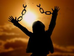 freedom, silhouette of woman with broken chain on hands at sunset sky