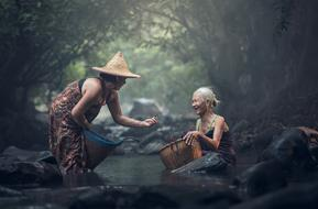 two happy senior Asian women Bathing a forest