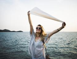 joyful girl in outstretched arms holds a white flag