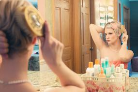 blonde combing her hair in front of a mirror