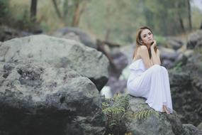girl in a white dress sits on a boulder on the shore of the pond