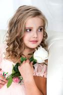 girl with curly hair and a white rose