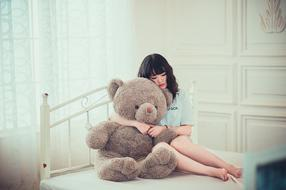 Asian girl with a teddy bear on the bed