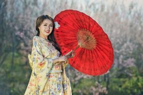 happy young asian woman in kimono posing with traditional red umbrella
