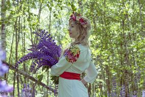 photo of a girl in a russian folklore costume with a purple bouquet of flowers