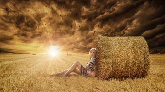 Woman Sitting on harvested field leaning to hay ball at sunset