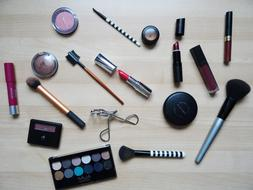 makeup brushes, shadows and lipstick on the table