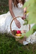 bride with a basket of fruit on a green meadow