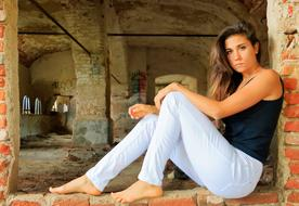 young Woman sits in window hole of ruined building