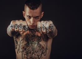 photo of a guy with tattoos and rings