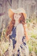 Beautiful happy redhead girl in wide hat at Summer