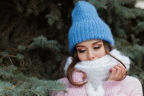 young Woman in winter clothe at fir tree, Portrait