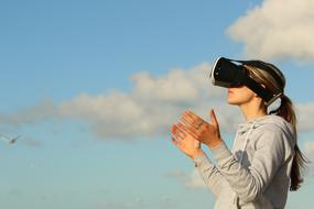 girl in virtual reality glasses against the blue sky