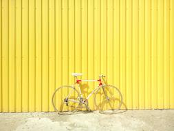 bicycle parked by the yellow wall