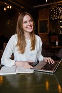 photo of happy female student with laptop and abstract in cafe