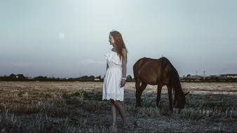 young Girl and grazing horse on harvested field at dusk