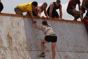 men helping to Girl on Mud Run