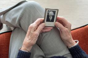 elderly man's hands hold a black and white photo